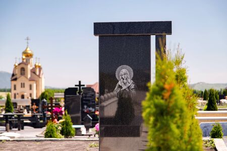 Black marble tombstone with an image of an Orthodox icon. Cemetery of the mountainous region of the Caucasus