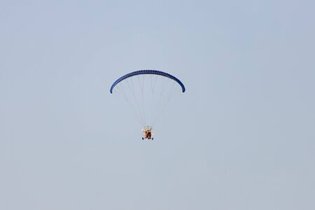 Tourists fly on motorcycle paragliders over the mountain range