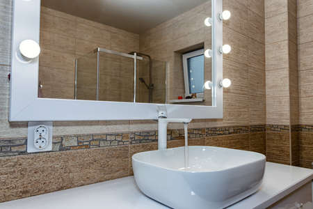 The interior of the bathroom with a big illuminated mirror, walk-in shower and elegant sink