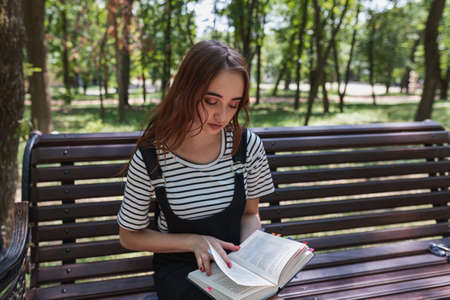 Charming redheaded teen girl in the Park reading a book on a bench and preparing for the exam