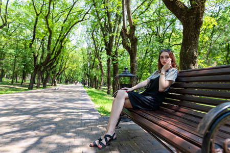 Charming red-haired girl sitting on a bench in a Park and talking on a mobile phone