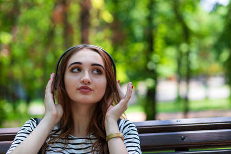 A young pretty red haired girl is listening to music with headphones while sitting on a Park bench Foto de archivo