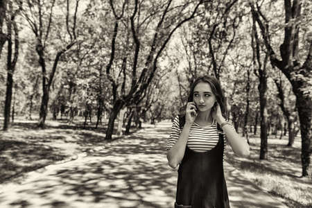 A charming redheaded teen girl is walking through a city Park and talking on her mobile phone.