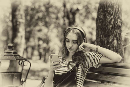 A young pretty red haired girl is listening to music with headphones while sitting on a Park bench Stok Fotoğraf - 152322308