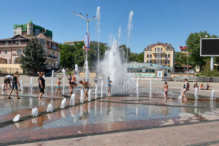 ESSENTUKI- AUGUST 19: Children play under the fountain in the Central square at the entrance to the resort Park. August 19, 2020 in Essentuki, Russia. Stok Fotoğraf - 154118633