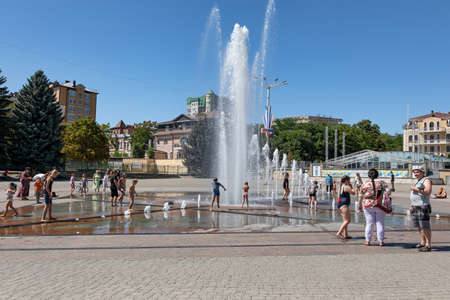ESSENTUKI- AUGUST 19: Children play under the fountain in the Central square at the entrance to the resort Park. August 19, 2020 in Essentuki, Russia. Stok Fotoğraf - 154118687