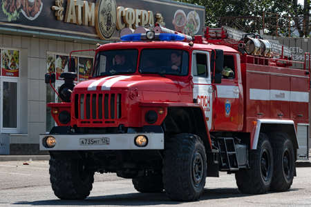 MINERALNYE VODY - SEPTEMBER 05: A large red fire truck on the Ural 4320 chassis is driving along the road to an emergency call. September 05, 2020 in Mineralnye Vody, Russia. Stok Fotoğraf - 155244933