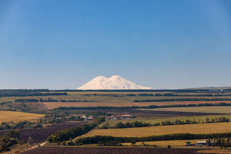 View of the snow-covered slopes of Elbrus from the agricultural fields