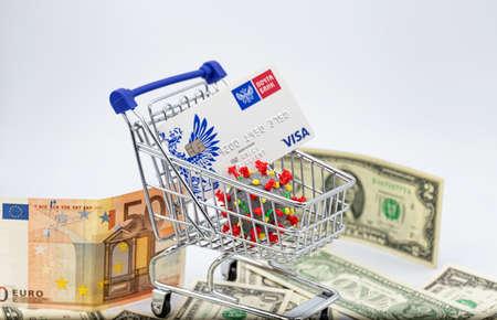 ESSENTUKI - SEPTEMBER 20: A model of coronavirus in a shopping cart and a VISA Bank card. September 20, 2020 in Essentuki, Russia. Stok Fotoğraf - 155755717