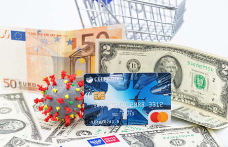 ESSENTUKI - SEPTEMBER 20: A model of coronavirus in a shopping cart and a VISA Bank card. September 20, 2020 in Essentuki, Russia.