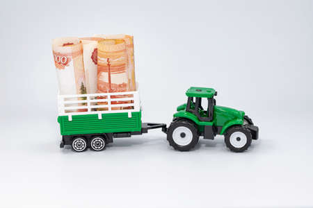 A toy green farm tractor carries five-thousand-ruble bills rolled into a tube in a trailer