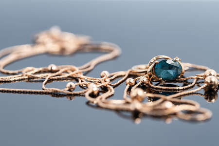 A gold chain with a pendant and a Topaz ring lie on a dark reflective surface