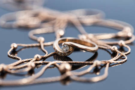 A gold ring with diamond and a gold chain necklace lie on a dark reflective surface