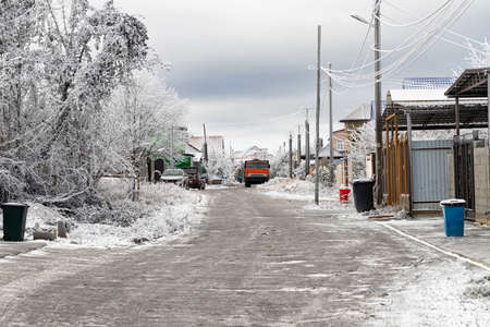 Street of a cottage village with frozen wires on poles, ice on the road and icy trees Stok Fotoğraf