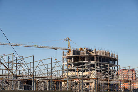 Construction site of a multi-storey monolithic house with a yellow tower crane Stok Fotoğraf