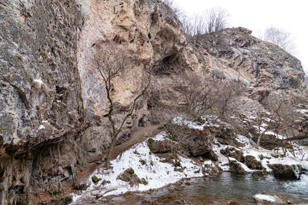 The waterfalls, which are not completely frozen in winter, flow down from the porous rocks