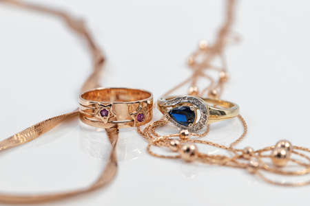 Two different-shaped gold rings with precious stones and two completely different-shaped gold chains