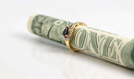 A gold sapphire ring is worn on a dollar bill rolled up into a tube Archivio Fotografico