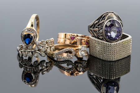 Gold and silver rings of different shapes and with different precious stones Archivio Fotografico