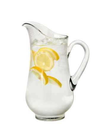 glass water pitcher with slices of lemon and ice photo