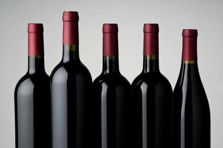 various sizes and varietals of wine bottles,neutral background,mostly front bottle is sharpest