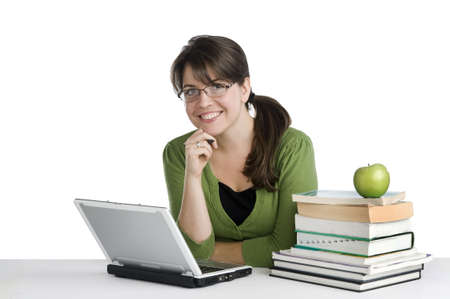 young woman looking like a studentteacher, with laptop, stack of books,green apple