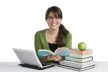 young woman looking like a studentteacher, with laptop, stack of books,green apple photo