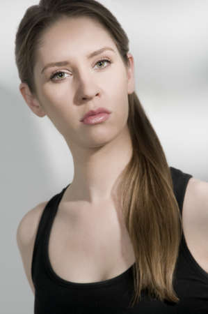 pony tail: sexy young female model,pony tail,black tank top,serious expression with eye contact,snappy lighting Stock Photo