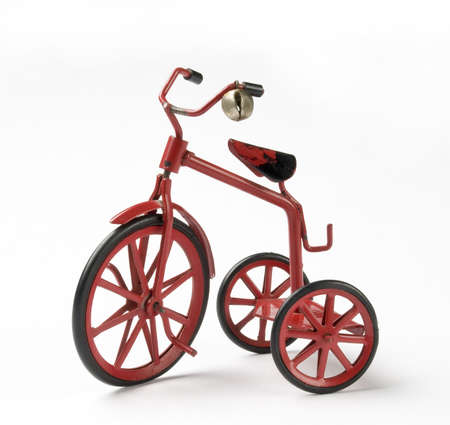 antique tricycle: tiny red toy vintage metal tricycle on white background