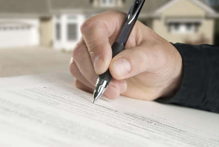 man signing paperwork, new home in background photo