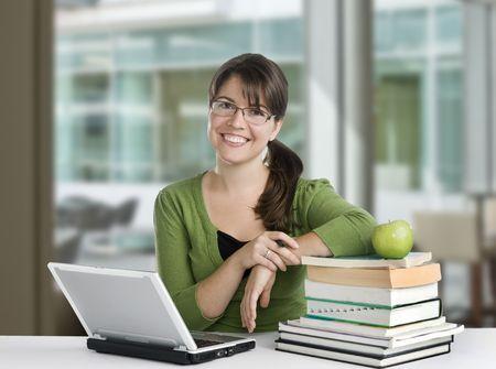 docenten: jonge vrouw die zich voordeed als een student of docent met boeken, laptop en appel, dragen bril en groene top