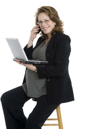 pregnant business woman in her forties, holding cell phone and laptop, glasses, sitting, wearing black suit, isolated on white photo