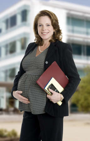 brunette business woman, mid 40's, holding note books and phone, building in background Stock Photo - 8552333