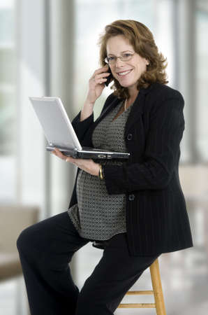 pregnant woman in her 40s, with laptop, phone, sitting in office photo