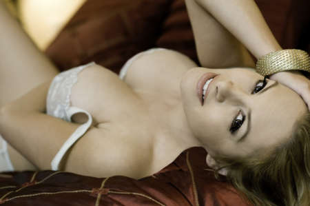 sexy beautiful woman lying down wearing lingerie, one piece of jewelry