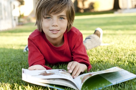Very cute 7 year old boy lying on the grass reading a kids book photo