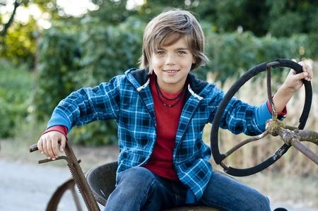 farm boys: happy 7 yr old boy having fun sitting on old farm tractor, plaid jacket and jeans