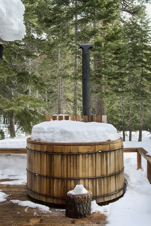 Nice wooden hot tub covered with snow, winter background, northern california photo
