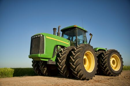 Looking up at green farming tractor with rice field in the background Editorial