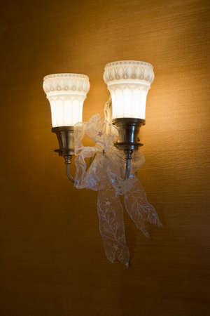 wall sconce: Antique wall sconce lights with gold wall paper, decorated with holiday ribbon