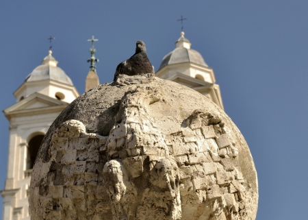 spanish steps: Pigeon on top of carved bird-rock with church in the background at the Spanish Steps in Rome  Stock Photo