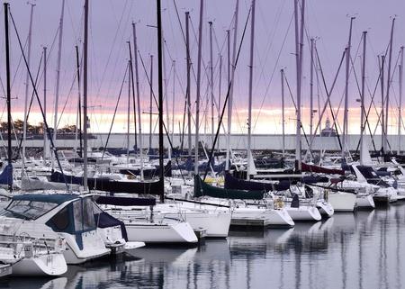 lake michigan lighthouse: Barcos en el puerto en el lago Michigan al amanecer con rotura de la pared y el faro en el fondo Foto de archivo