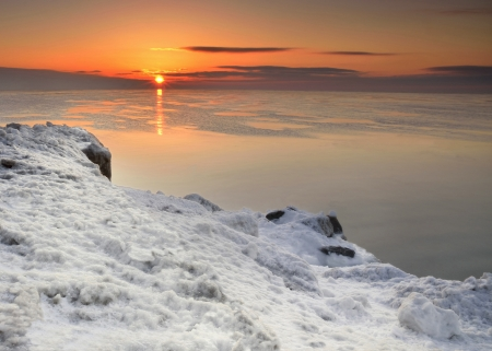 michigan snow: Early sunrise in winter over Lake Michigan with a snow capped shoreline
