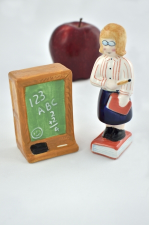 Ceramic teacher standing on book with pencil next to a ceramic chalkboard with numbers and letters written in chalk with real apple in background.  photo