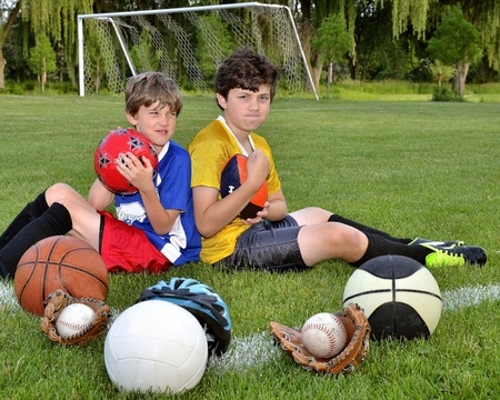 favoring: Young brothers with backs to each other on a soccer field, surrounded by various sports equipment, favoring a sport while looking competitive  Stock Photo