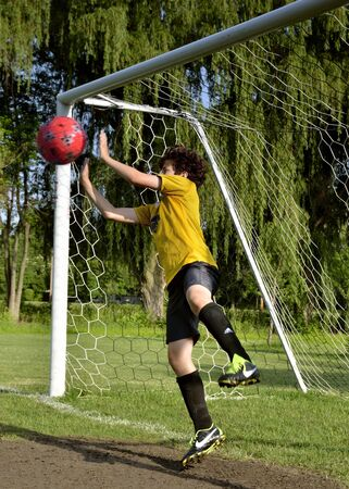 Young boy airborne protecting the soccer goal by blocking a shot taken on goal
