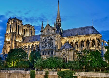 buttresses: Dusk picture of Notre-Dame Paris France with streaking clouds, illuminated tower and buttresses.