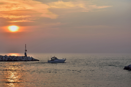 lake michigan: Sunrise over Lake Michigan in Winthrop Harbor Illinois with a recreational fishing boat pulling out of the protected harbor.