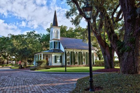 country church: Charming southern community in South Carolina with gas lit lamps, moss filled trees, and beautiful country church. Stock Photo