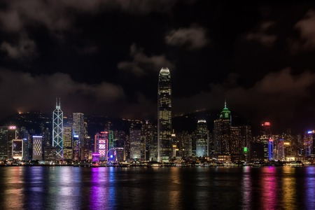 encircling: Hong Kong Harbor skyscrapes late into the evening with colored lights reflecting off the bay and clouds  encircling the moutains and sky.